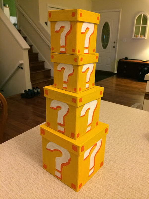 Super Mario Style Question Mark Boxes. These cardboard boxes are painted yellow with the yellow color first and question marks. They are used for a super mario baby shower.
