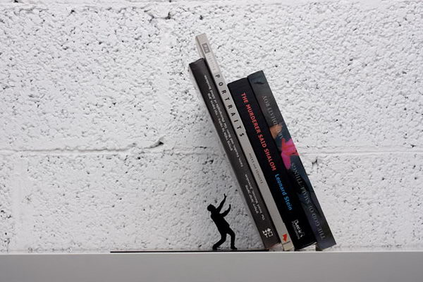Falling Bookend. The heavy books appear to almost crush the handsome little man, but don't worry   the sturdy book end will keep your books tidy and upright.