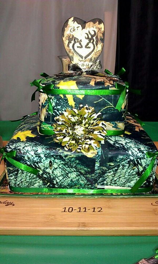 Camouflage wedding cake with an orange flower and ribbon.