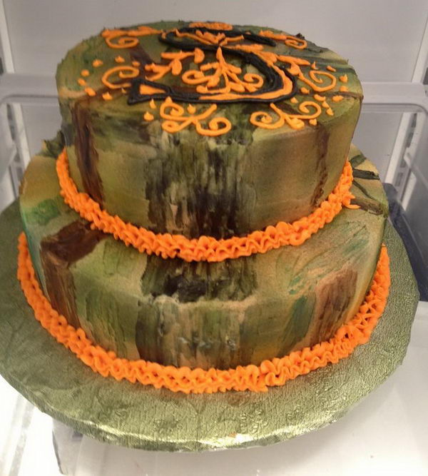 Camouflage wedding cake with initial piped in frosting on top tier.