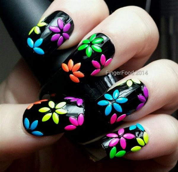 3D Nail Art with Colored Flowers on Black Background, 3D nail art is a technique for decorating nails that creates three dimensional designs.