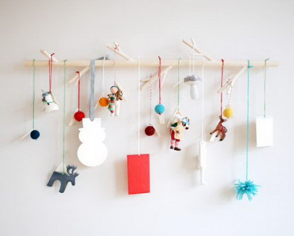 Ornaments hung from a branch as a modern advent. This advent calendar is a fun, popular way for kids and adults to count down the days until Christmas. Kids would love the surprises hidden behind each day.