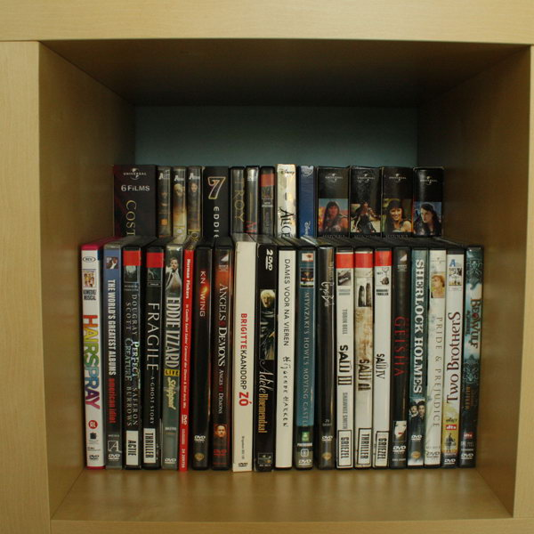 Double DVD storage space by placing a raised shelf in the back of a bookcase.