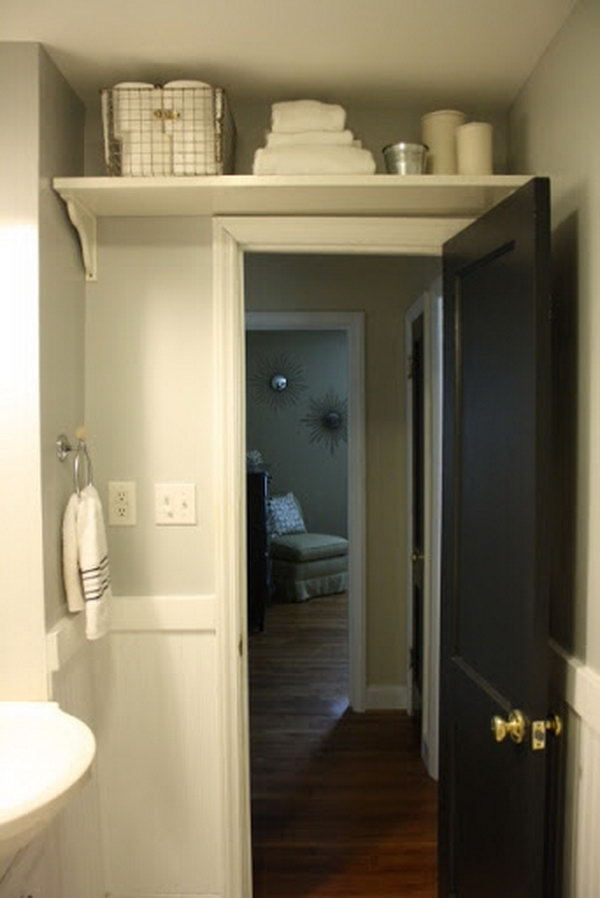 Store bathroom extras like toilet paper and extra towels with the shelf above the door.