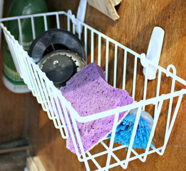 Hang a simple dollar store basket on the inside of your cabinet door. It's a clever under sink storage idea for wet sponges and brushes and give them air to dry.