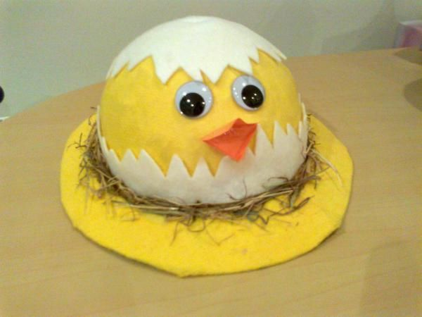Chicken Styled Easter Bonnet. This adorable Easter bonnet with chicken style is made up of yellow and white craft paper. Glue the eye and mouth, then put some straws to decorate it.