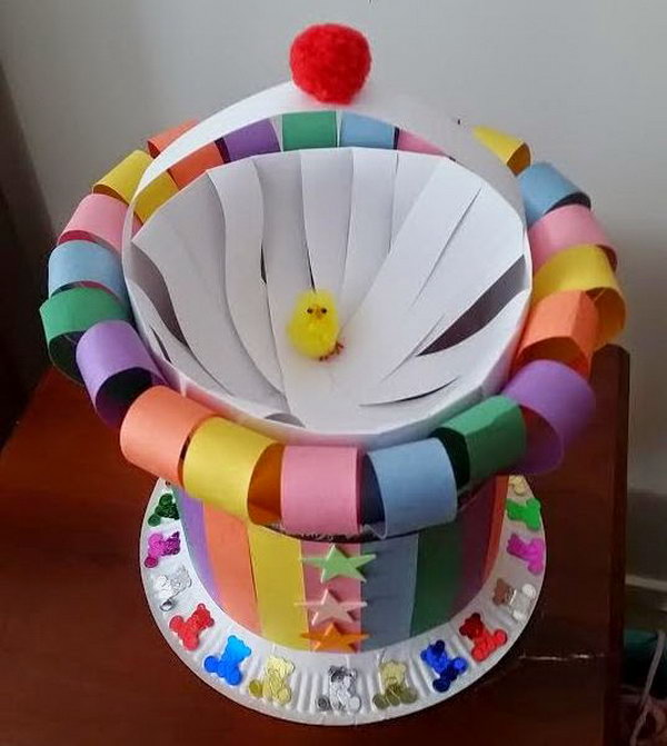 Colorful Strips Easter Bonnet. Roll the paper into a cylinder and cut the strips, glue the opposing ends and leave one to make the handle. Cut colorful strips to apply this pattern around the cylinder. Stick this with the plate and finish off this Easter hat with some foam stars or teddy confetti.