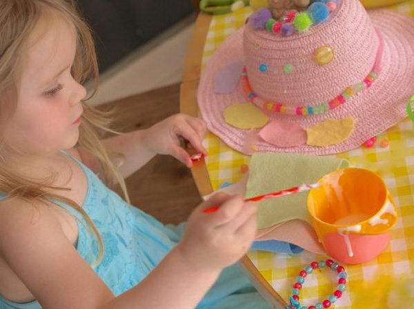 Lovely Easter Bonnet DIY by a Little Girl. I just can't believe my eyes. The lovely girl can DIY such a beautiful craft all by herself. She is trying to stick the pattern around the brim and add the beading and pom poms to decorate her bonnet for the girls Easter bonnet competition at her school.