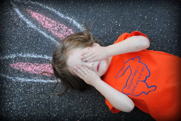 Funny Bunny Ears Easter Photo. The little girl wearing a red T shirt with a bunny patter is lying on the ground with the bunny ears drawing beforehand. I really love this Easter photo idea, it's full of creation and imagination.