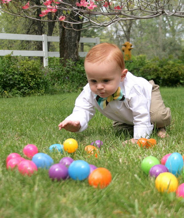Adorable Easter Happening. Throwing some colorful plastic Easter eggs on the lawn. The kid must be eager to hold the colorful eggs. When he is crawling to catch one, take the shoot.