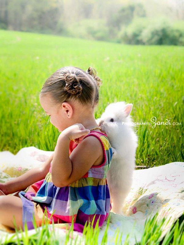 Funny Easter Bunny Picture. The little girl with beautiful dress is sitting on a blanket, the cute bunny is trying to bite her necklace from the back. It's so wonderful to witness this interesting moment.