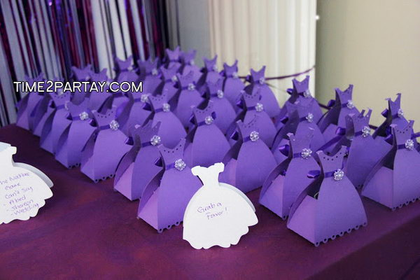 Purple Dress Favors. Personalize your Engagement party favors by designing them in the purple dress flavor with tiny beading flower embellishment and ribbon bows tied along the waist line. These favors are filled with chocolate of course.