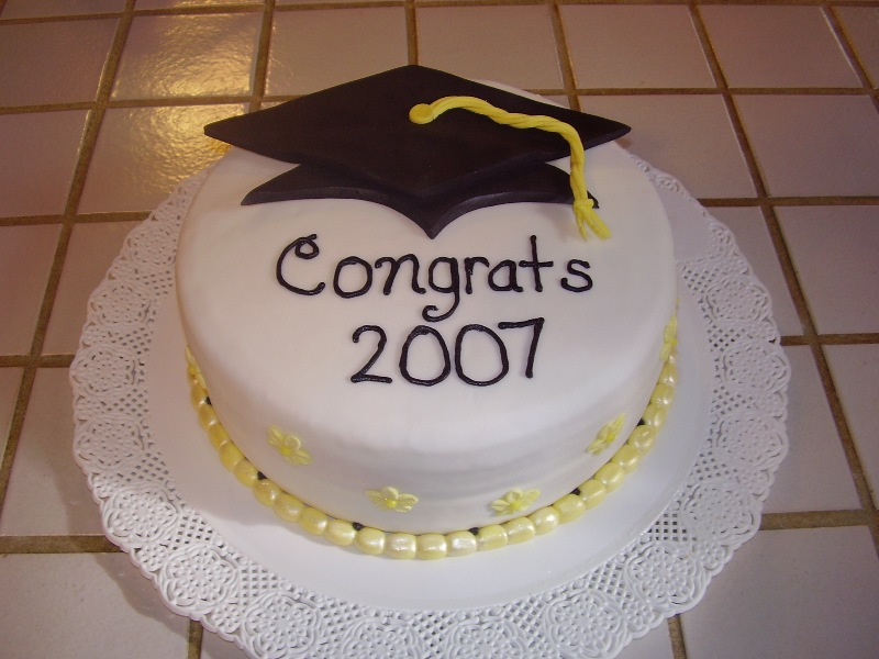 Nurse Graduation Cake. This nurse graduation cake has a graduate's cap at the top, a circle of pearl candies at the bottom as well as some floral decoration at the side for beautiful garnishment. The graduate must adore this sweet and elegant graduation cake.