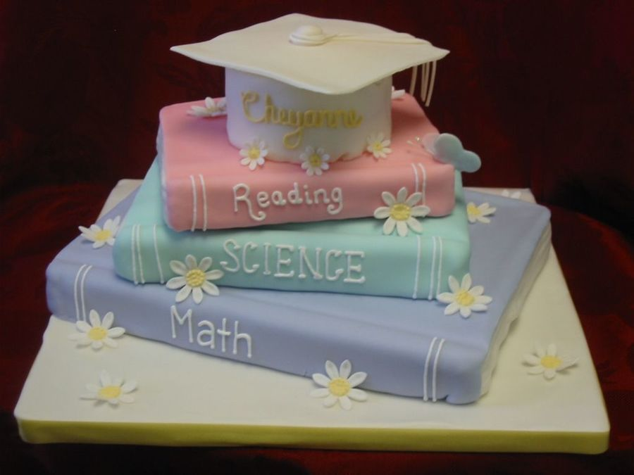 Stacked Book Graduation Cake. This adorable graduation cake features a stacked book design in soft colors. It is made up of chocolate fudge, vanilla fondant as well as beautiful gumpaste flower and butterfly.