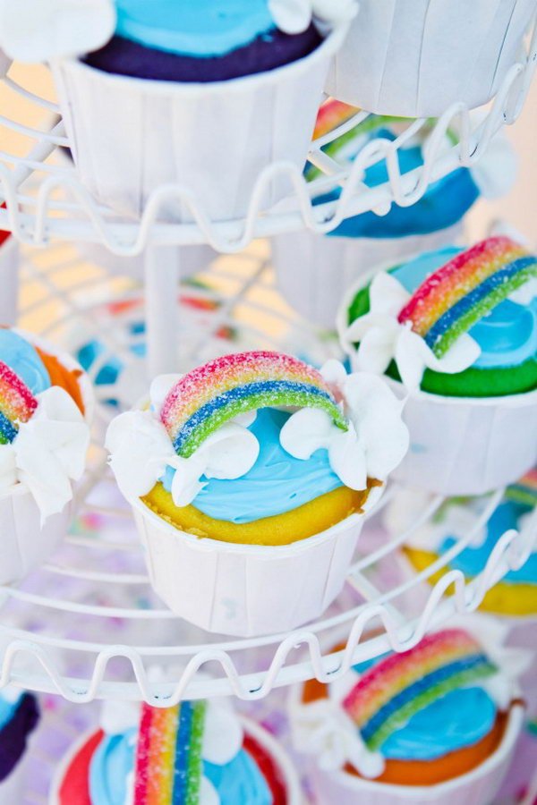 Serve your party with these colorful rainbow cupcakes. Put together all the rainbow cupcakes along the shelf. Decorate the cupcakes with sour rainbow candy and frosting clouds.