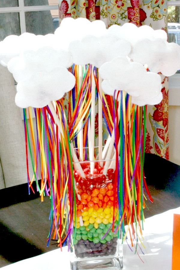 Fill the glass jar with candies layers upon layers. Add some decorations for beautiful outlook design such as white cute clouds and colorful ribbons on sticks. It can light up your party design style.