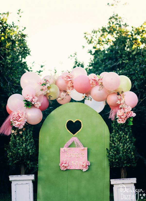 Fairy Gate Party Idea. Decorate your sweet and romantic party with this fairy gate. It has flower bushes in the balloon arch above the topiary. Below the balloon arch is the tall metal garden lantern stakes. I like this fairy style.
