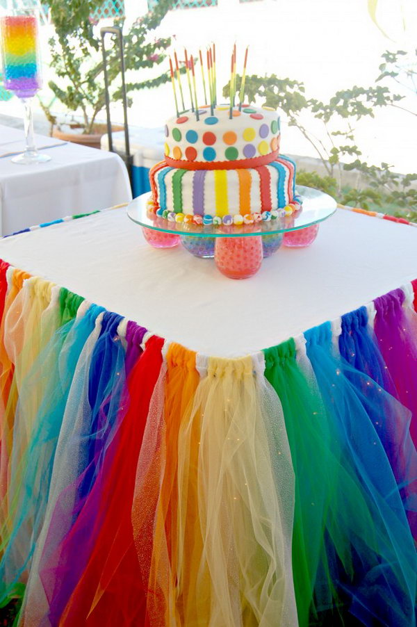 Table Skirt Party Idea. Cover your table with a tablecloth, pin the elastic to the tablecloth and attach the tulle to the elastic. Tighten the tulle to look like a tie with the knot in the front. Apply some beadings to make it more colorful. It makes a fabulous statement for your party.