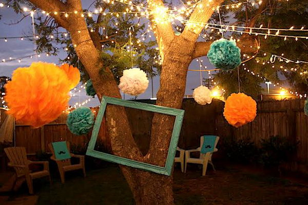 Lights and Tissue Paper Poms. This summer party features the elegant Christmas lights from trees and tissue poms on the strands to create an elegant decor. This decoration is fantastic to get everything dolled up for the summer party.