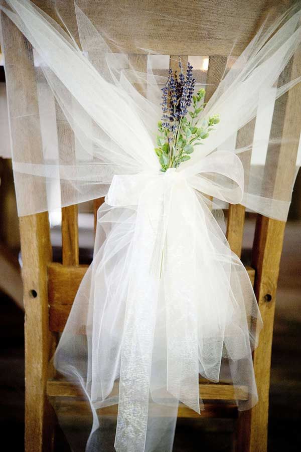 Lavender and Tulle Chairbacks. Tie lengths of ethereal tulle to the back of your chairs and attach colorful flowers such as lavender to match your wedding theme. I really adore this chair decoration for its romantic and dreamy style for wedding ceremony.