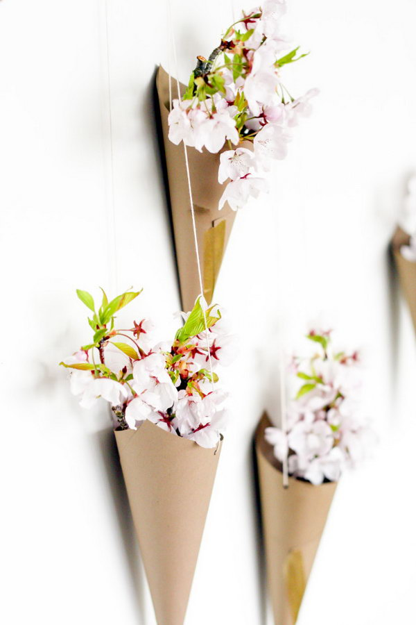 Blossoming Flower Cone Wall Display. Create cones from cardstock, punch 2 holes at both sides, take the string to hang the cone pointed-side down. Arrange the cones on the wall and place some flowers in them to create the beautiful wall art for your dorm room.