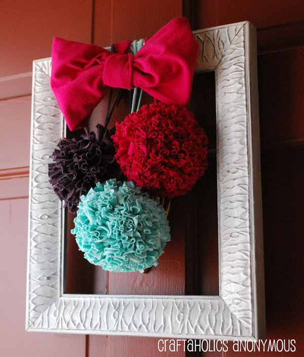 DIY T shirt Pom Poms. T shirt pom poms are so much more durable than tissue paper to hang on the door. They are so whimsical and fun and also great for adding color to any room. You can make some in different colors with the tutorials below.