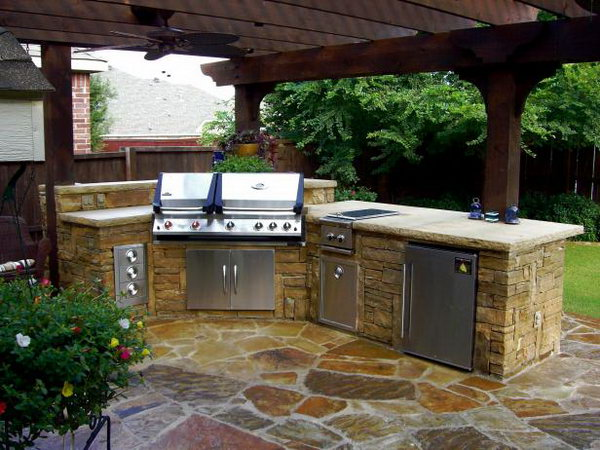 This stone outdoor kitchen features a refrigerator, grill, sink and storage, looking simple but fully functional. The wood roof and the stone structure are ideal and cool when cooking and dining during the summer night.