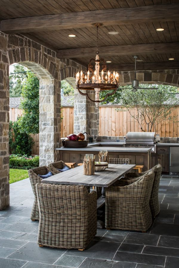 The chandelier adds some mystery and romance to this outdoor kitchen. The soft, warm lighting bright up the space and adds irresistible charm to these spring spots. It really fits with the foundation of rocks and grey brick.