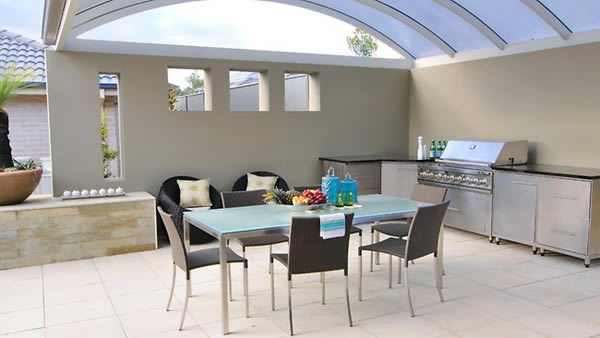 This is a typically modern outdoor kitchen with the glass roof and the grey, white and black elements.