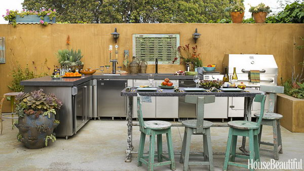 There's a feeling of some age and maturity to this outdoor kitchen designed by Sandy Koepke in Manhattan Beach, California. It is really a great place for a party with a stunning outdoor fireplace, earthy dicers and beer on tap.