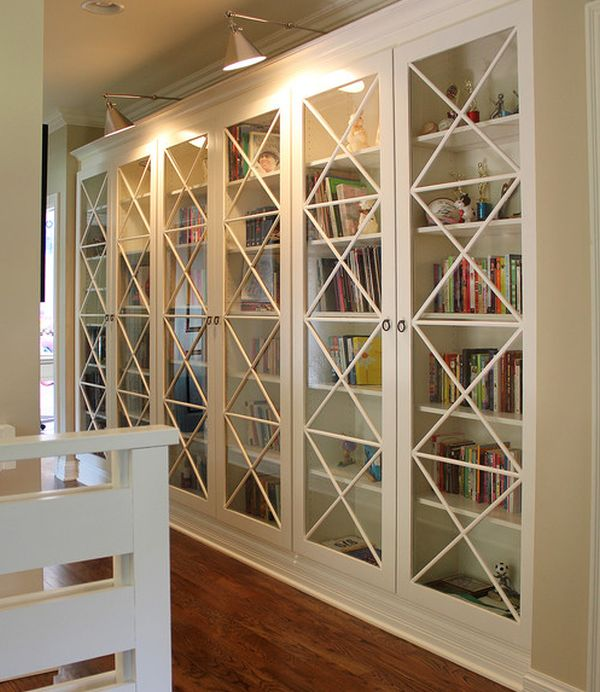 These X motif custom designed glass doors along with library lighting  give these bookcases an inimitable look. It is a simple way to ensure that your interiors stand out from the crowd. See more