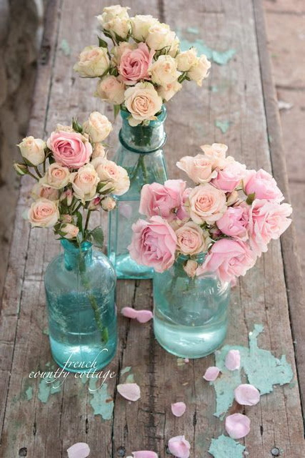 Vintage Blue Bottles. The bottles pair so well with the spray roses, and the color of these bottles is lovely.