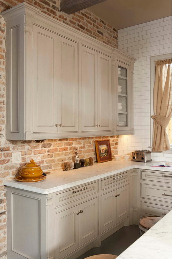 Gray Kitchen Cabinet Against Brick Backsplash And White Honed Carrara