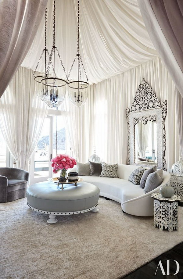 This living room is tented with a sheer fabric of design, and grouped a vintage sofa with a Levantine mirror and a rug. So gorgeous!