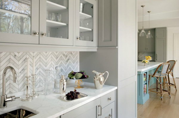 Marble Tiled Chevron Backsplash with Light Grey Cabinetry