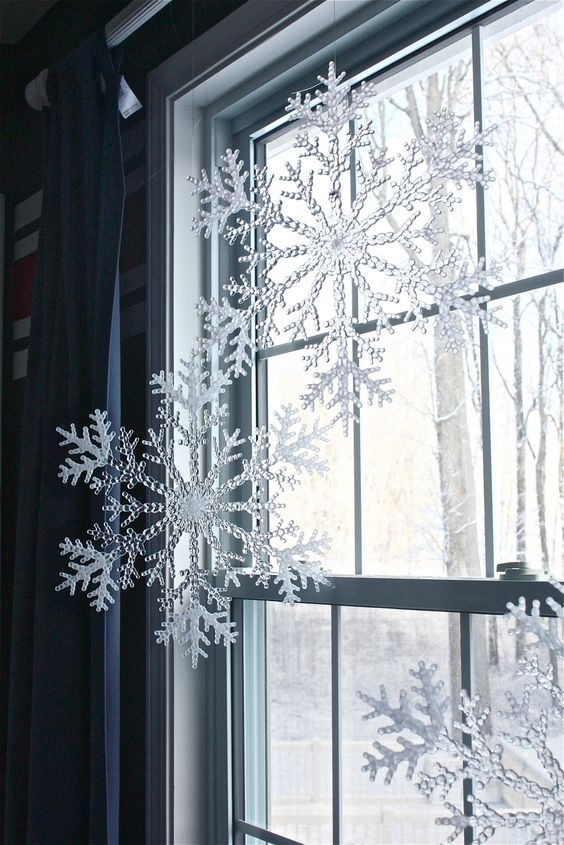 Plastic Snowflakes from Dollar Tree Hung from Curtain Rod with Fishing Wire.