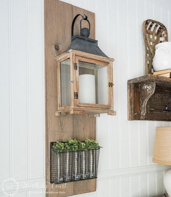 Farmhouse Style Lantern Hanging and Wire Basket Filled with Vases and Sprigs of Greenery.