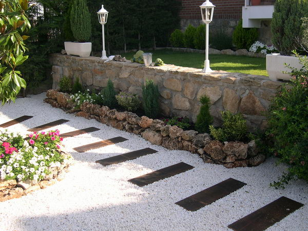 Grate Landscaping with White Gravel and Wooden Panels Pathway.