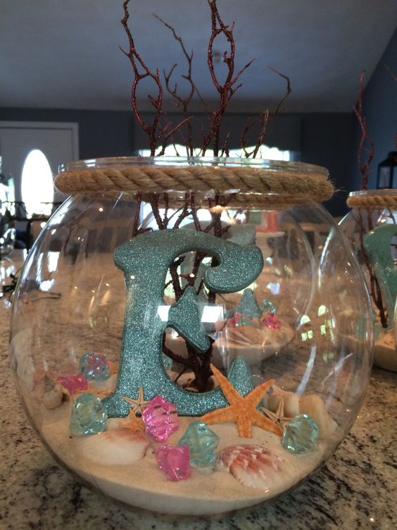 Seashells And Sand Displaying In A Fish Bowl.