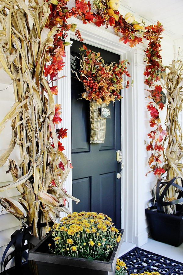 Fall Leaf Garland And Flower Pots With Corn Stalks Decorated Front Porch.
