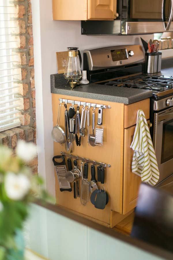 Attach hooks to hang kitchen utensils on the side of your cabinet.