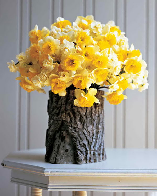 Log Vase with Yellow Flower Arrangement.