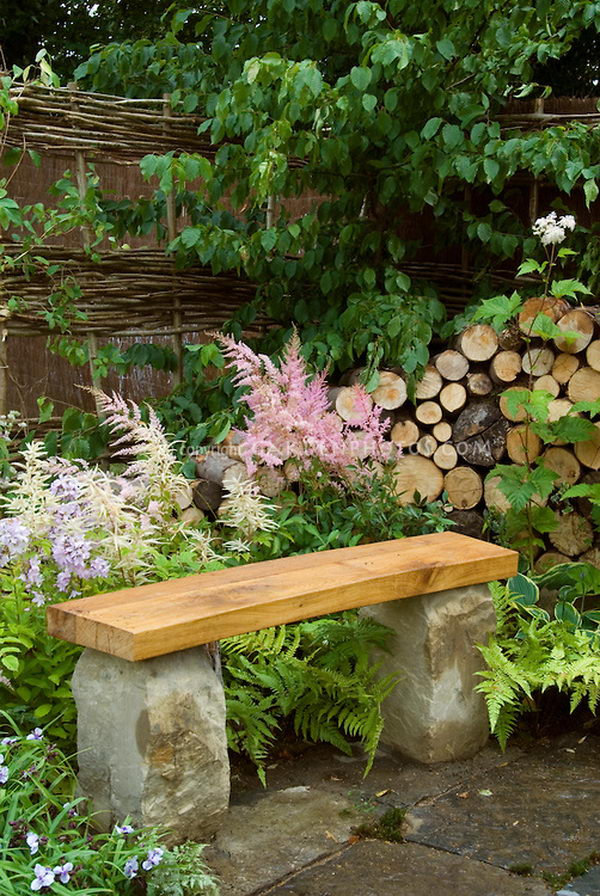 Stone and wood bench is a simple accent for the garden.